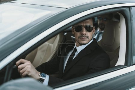 Photo for Bodyguard sitting in car with businessman and looking away - Royalty Free Image