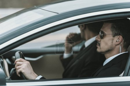 Photo for Bodyguards with portable radio and security earpiece sitting in a car - Royalty Free Image