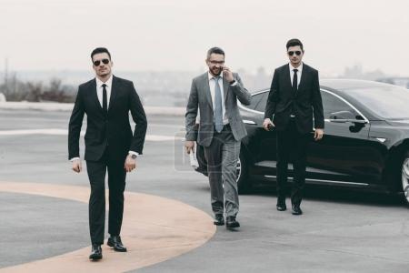 Photo for Smiling businessman walking with bodyguards from car and talking by smartphone - Royalty Free Image