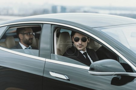 two bodyguards and businessman in glasses sitting in a black car