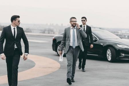 Photo for Businessman walking with bodyguards on helipad and talking by smartphone - Royalty Free Image