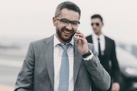 Photo for Smiling businessman with bodyguard talking by smartphone - Royalty Free Image