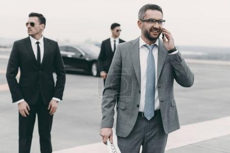 smiling businessman walking with bodyguards and talking by smartphone