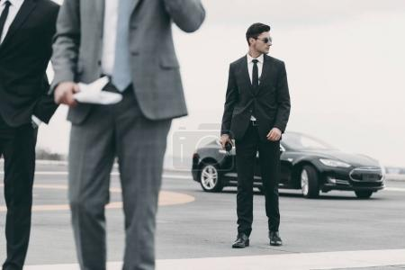 cropped image of bodyguards and businessman walking on helipad from car