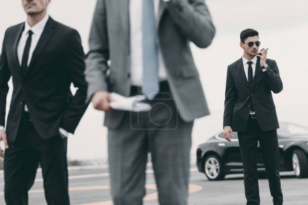 Photo for Cropped image of bodyguards and businessman walking on helipad - Royalty Free Image