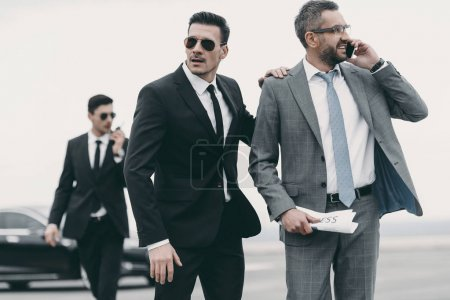 businessman walking with two bodyguards and talking by smartphone