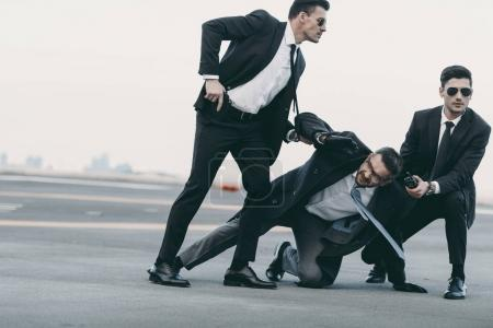 two bodyguards in sunglasses protecting falling businessman