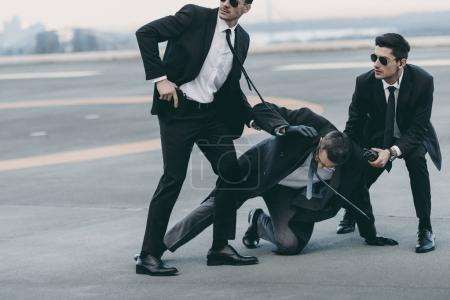 cropped image of two bodyguards protecting falling businessman