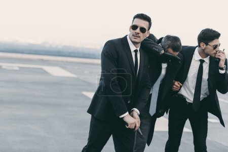 two bodyguards protecting businessman with gun