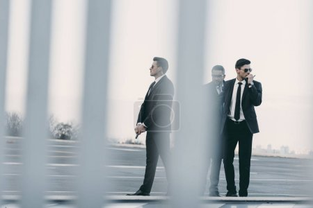 view through fence of businessman with bodyguards standing on helipad