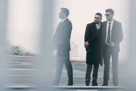 Photo for View through fence of bodyguards protecting businessman on helipad - Royalty Free Image