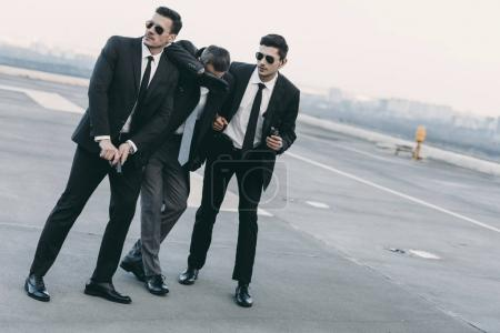 Photo for Two bodyguards in sunglasses protecting businessman with gun - Royalty Free Image