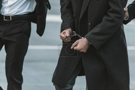 Cropped image of security guard holding man in han...