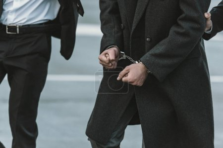 Photo for Cropped image of security guard holding man in handcuffs - Royalty Free Image