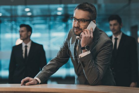 businessman talking by smartphone and standing at reception counter