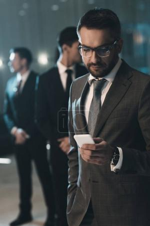 Photo for Handsome businessman standing and looking at smartphone - Royalty Free Image