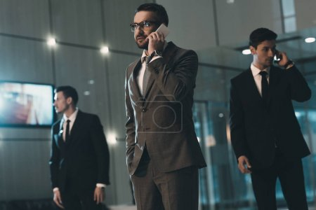 Photo for Businessman talking by smartphone in business center - Royalty Free Image