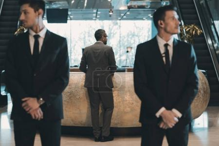 Photo for Businessman standing at reception counter in business center - Royalty Free Image