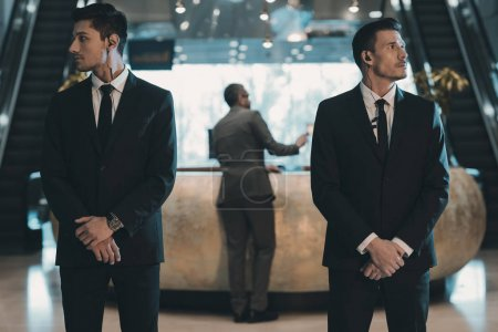 two bodyguards waiting for businessman standing at reception counter
