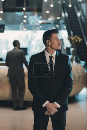 Photo for Handsome bodyguard waiting for businessman at business center - Royalty Free Image