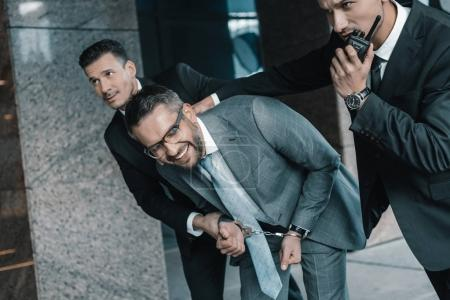 Cropped image of security guards arresting laughing criminal