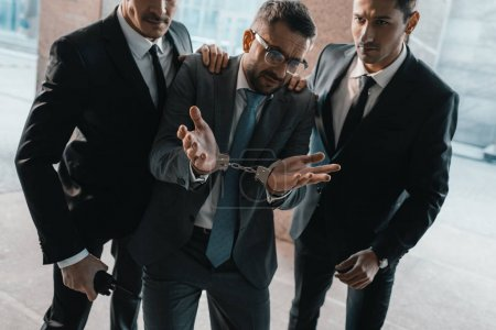 Photo for Arrested offender showing security guards shrug gesture - Royalty Free Image