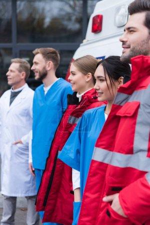 Photo pour Vue latérale d'ambulanciers paramédicaux travaillant debout de l'équipe en face de la voiture - image libre de droit