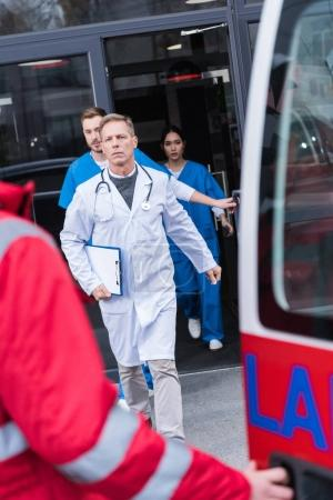 serious doctors going from hospital to ambulance