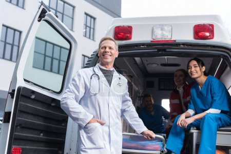 smiling paramedic team with working car