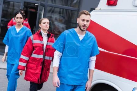 young male and female paramedics walking near ambulance
