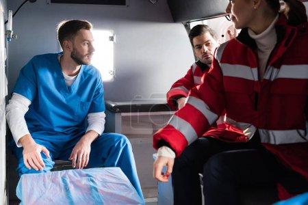 Three ambulance doctors sitting in a car