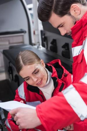 attractive male and female paramedics reading documents in front of ambulance
