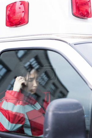 young female Asian paramedic reading something in ambulance