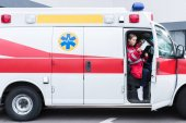 young male and female paramedics sitting in ambulance