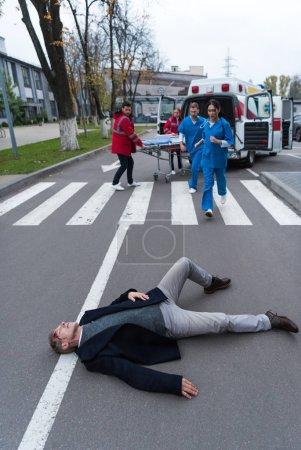 paramedics running to help injured man lying on a street
