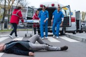 cropped image of doctors going to wounded middle aged man lying on a street