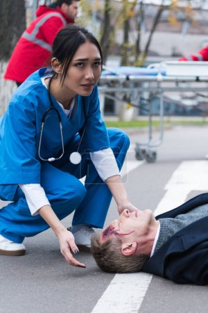 young female Asian doctor helping unconscious injured man lying on a street