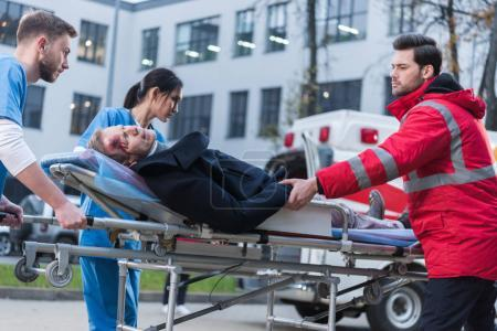 doctors moving injured man on ambulance stretcher