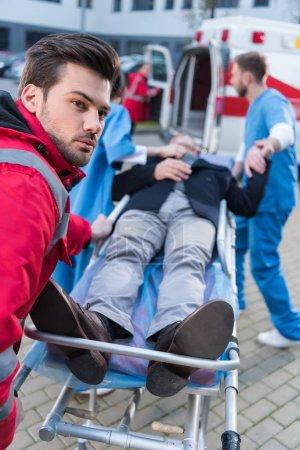 Paramedics moving ill man on ambulance stretcher