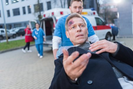 scared injured man with wound on head lying on ambulance stretcher
