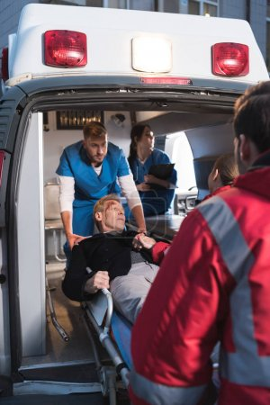 Photo for Paramedics moving injured man into ambulance - Royalty Free Image