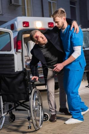 paramedic helping injured patient to sit in wheelchair