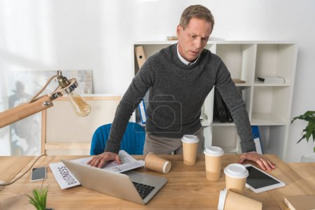 mature man feeling bad and leaning on table in office
