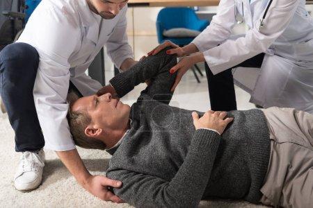 Photo pour Cropped image des médecins aidant l'homme est tombé - image libre de droit