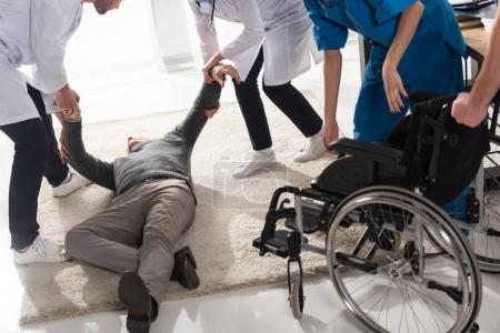 Photo pour Image recadrée de médecins aidant l'homme inconscient dans un hôpital - image libre de droit
