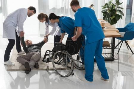 doctors helping fell mature man to sit on wheelchair