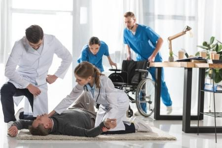 Photo for Young doctors checking pulse of unconscious man lying on a floor in hospital - Royalty Free Image