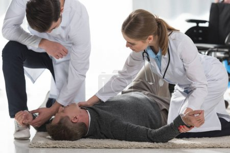 doctors checking pulse of unconscious man