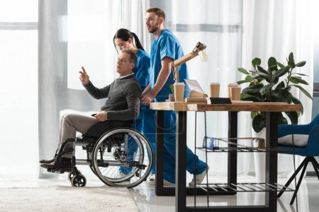 Nurses helping middle aged man on wheelchair
