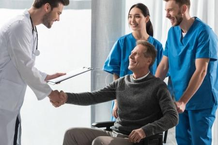 smiling doctor and patient on wheelchair shaking hands